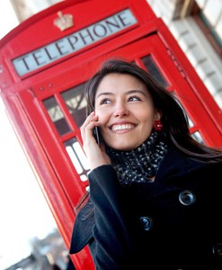 beautiful woman talking on the phone with a London phonebox behind her